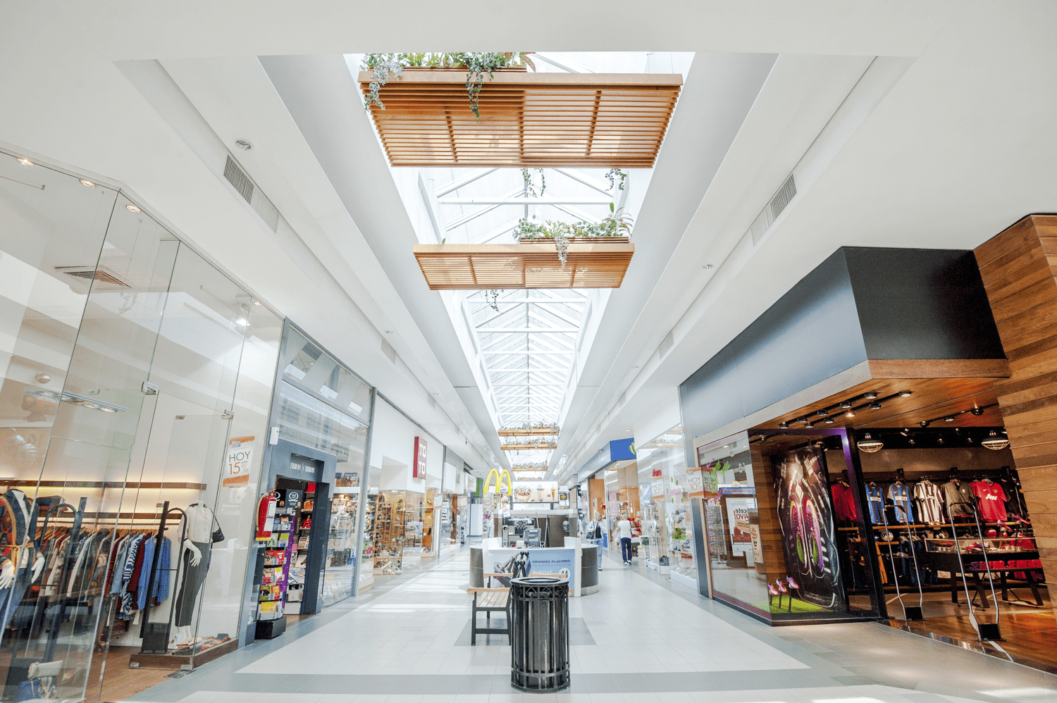 interior of a shopping mall looking down the corridor with glass exterior stores on either side. seating, trash cans and kiosks in the center