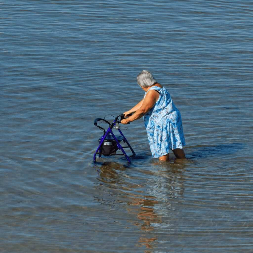 senior age female is a sleeveless blue pattered dress, sing a walker with wheels, moving through knee deep water