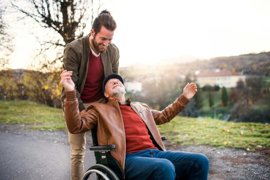 caucasian adult senior male seated wearing blue jeans, a red sweater, tan jacket and a black hat, leaning back in his wheelchair with his arms spread, looking up at a younger adult male standing behind him, wearing tan pants, a red shirt and a tan jacket looking down at the seated man outdoors on a paved path with grass, trees, a body of water, and the sunset in the background