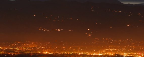 nighttime distance shot of the lights of boulder with sunset behind the mountains in the background