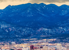 distance shot of the skyline of Colorado Springs with snowy mountains in the background
