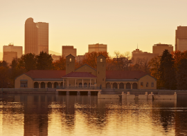 city park lake and park with the Denver skyline behind in the warm yellow glow of sunset